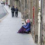 Mendigo fêmea que senta-se no pavimento que guarda um copo imagens de stock