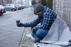 Mendigo Holding Disposable Cup imagen de archivo libre de regalías