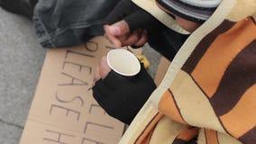 Mendigo masculino que conta o dinheiro e que põe no copo de papel, na tristeza e na pobreza vídeos de arquivo