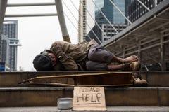 Mendigo o sueño sin hogar del hombre en ciudad en el invierno foto de archivo libre de regalías
