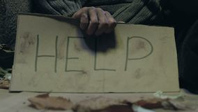 Mendigo que lleva a cabo la muestra de la ayuda, el problema de la pobreza y la falta de vivienda en las calles de la ciudad metrajes