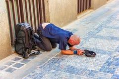 Mendigo sin hogar enfermo en sus rodillas en la ciudad vieja de Praga imágenes de archivo libres de regalías