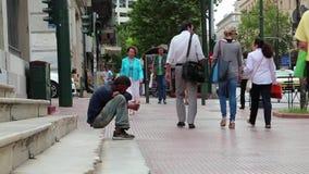 Mendigo y gente en la calle en Atenas, Grecia