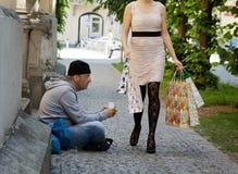 Mendigos y mujer rica con los bolsos de compras Imagenes de archivo