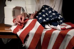 Mending America. Close up of a woman's hands mending a tattered American flag on a sewing machine Royalty Free Stock Photo