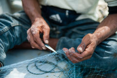 Mending fishing net Royalty Free Stock Image