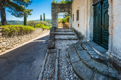 MENERBES, FRANCE - MAY, 2015: Old porch with stairs and emerald stock image