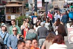 Menge des Leute-Wegs unter Laufkatzen-Autos in San Francisco Lizenzfreie Stockfotografie