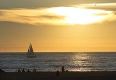 Menge und Segelboot bei Sonnenuntergang Lizenzfreie Stockfotos