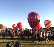 Menge von Ballonen der Leute und der Heißluft Stockfotos