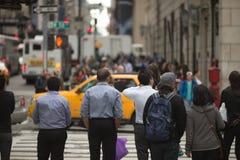 Menge von den Leuten, die auf Straßenbürgersteig gehen Stockbild
