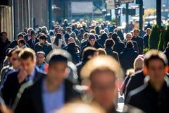 Menge von den Leuten, die auf Straßenbürgersteig gehen Lizenzfreie Stockbilder
