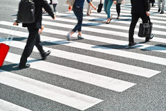 Menge von den Leuten, die auf Zebrastreifen Straße gehen Stockfoto