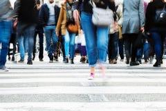 Menge von den Leuten, die eine Stadtstraße kreuzen Lizenzfreies Stockbild