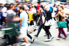 Menge von den Leuten, die eine Straße in der Stadt kreuzen Stockbild