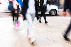 Menge von den Leuten, die eine Straße mit Zoomeffekt kreuzen Stockfoto