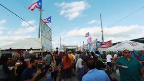 Menge von den Leuten, die herum während des Festivals gehen Puertorikanische Flaggen stock footage