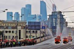 Menge von den Leuten, die rote Ballone halten, grüßt viele Autos, welche die Stadtstraßen waschen Stockbild
