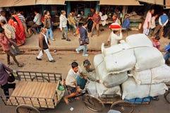 Menge von Leuten auf schmaler Straße mit Märkten, Speichern und Frachtarbeitskräften Lizenzfreies Stockbild