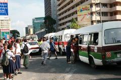 Menge von Leuten an einer Bushaltestelle während der Hauptverkehrszeit Lizenzfreies Stockbild