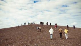 Menge von Leuten gehen herauf einen Hügel Stockbild