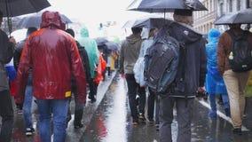 Menge von Leuten gehen, im Regen mit Regenschirmen zu arbeiten stock footage