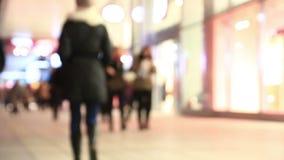 Menge von Leuten verschiebt sich auf Stadtstraße am Winterabend stock video footage