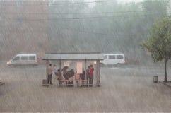 Menge von Leuten verstecken sich vom starken Regen an einem Halt in der Stadt Lizenzfreie Stockfotografie