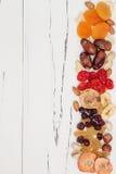 Mengeling van droge vruchten en noten op een witte uitstekende houten achtergrond met exemplaarruimte Hoogste mening Symbolen van Stock Foto's