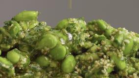 Mengeling van edamame met sesamzaden en avocado en olijfolie het gieten op het stock video