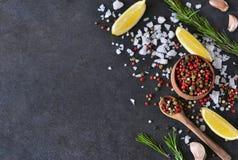 Mengeling van peper met zout, rozemarijn en knoflook op schaliesteen Stock Afbeeldingen