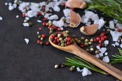 Mengeling van peper met zout, rozemarijn en knoflook op schaliesteen Stock Foto