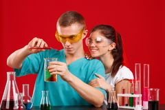 Mengen de het twee laboratorium hulpmeisje en jongen, verschillende vloeistoffen van verschillende flessen Op een rode achtergron Stock Foto