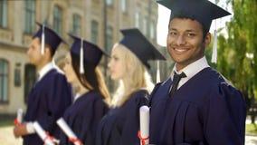 Mengen-ras gediplomeerde student die met diploma in camera, uitwisselingsprogramma glimlachen stock afbeelding