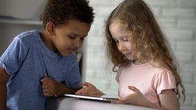 Mengen-raskinderen die op hun favoriete beeldverhalen op tablet, toepassing letten stock foto's