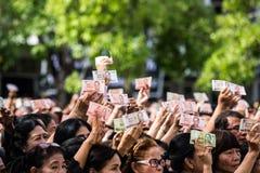 Mengen von Trauernden halten thailändisches Bargeld für Showbild von König Bhumibol während der Trauerzeremonie Stockfotos