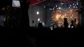 Mengenleute am Lebensstilmusikkonzert Jubelnde Menge macht Fotos auf einem Smartphone vor hellem buntem stock footage