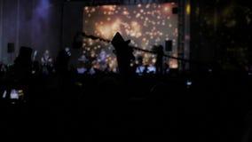 Mengenleute am Musikkonzert Jubelnde Menge macht Fotos auf einem Smartphone vor hellen bunten Stadiumslichtern stock video footage