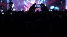 Mengenleute am Musikkonzert Jubelnde Menge vor hellen bunten Stadiumslichtern Lebensstilschattenbilder von stock video
