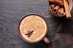 Mengt de chai latte traditionele warme Indische zoete melk gekruide drank van de Masalathee, gember, cinammon stokken, kruiden or Stock Afbeeldingen