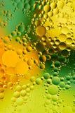 Mengt water en olie, mooie kleuren abstracte die achtergrond op groene en gele cirkels, ovalen, macroabstractie wordt gebaseerd Royalty-vrije Stock Foto