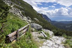 Mengusovska dolina, important hiking trail to hight mount Rysy, High Tatra mountains, Slovakia, amazing view with green hills. And blue sky, wooden barrier royalty free stock image