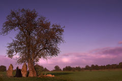 Menhir visit. Black caped woman visiting a group of three menhirs and a solitary tree stock photo