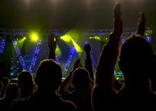 Menigte bij muziekoverleg, mensensilhouetten backlit door stadiumlichten royalty-vrije stock afbeeldingen