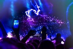 Menigte bij overleg Mensensilhouetten op backlit door heldere blauwe en purpere stadiumlichten Het toejuichen van menigte in kleu stock foto