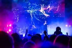 Menigte bij overleg Mensensilhouetten op backlit door heldere blauwe en purpere stadiumlichten Het toejuichen van menigte in kleu royalty-vrije stock foto's