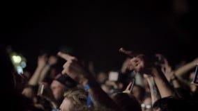 Menigte die hun handen opheffen en bij rotsoverleg bij nacht toejuichen stock video
