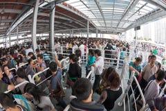 Menigte die omhoog buiten ingang van Wereld Expo binnen een rij vormen Stock Foto's