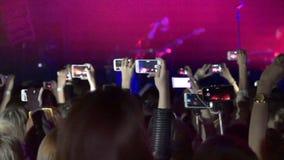 Menigte die partij maken bij rotsoverleg en handen vele camera's met digitale vertoningen onder mensen houden stock videobeelden