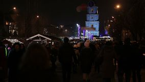 Menigte die van mensen die onderaan centrale straat lopen, Kerstmis van festiviteiten genieten stock videobeelden